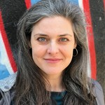 Megan Campisi, a white author with long, gray hair, smiles for the camera