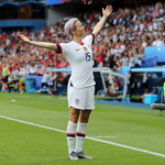 A photo of Megan Rapinoe, a white woman with dyed lilac hair, holding her arms out wide over the soccer field during the US Women's World Cup