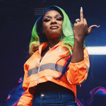 Megan Thee Stallion, a brownskinned Black woman with a blue and green weave, performs on stage