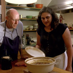 a bald, white man and a Brown woman with short, black, hair standing over a dish in the kitchen