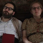a white couple sits beside each other on a bed in the new film Shirley