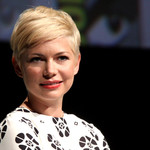 Michelle Williams wearing a black and white shirt, speaking on a panel at San Diego Comic Con