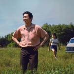 Set in the 1980s, the Yi family stands in a field in rural Arkansas. From left to right: Alan Kim skipping joyfully, Steven Yeun, in the foreground, puts his hands on his hips, Noel Kate Cho smiles and skips, and Han Ye-ri has her arms at her sides