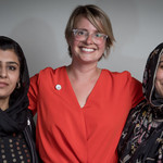 a tall, white woman with wire glasses is draped by two women of color wearing hijabs