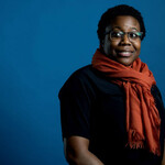 Moya Bailey, a Black woman with short black hair and glasses, poses against a blue background