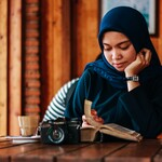 a brown-skinned woman wearing a hijab leans over as she reads a book
