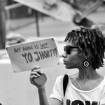 a Black woman with short, Brown, hair holds a My Name is Not Yo Shorty sign at a protest