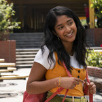 Maitreyi Ramakrishnan as Devi Vishwakumar, an Indian American girl, wears a backpack and smiles at school.
