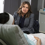 Mariska Hargitay, a middle-aged white woman with short, brown hair, sits in front of a hospital bed speaking to a victim on Law & Order: SVU