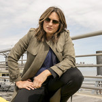Mariska Hargitay, a middle-aged white woman with short, brown hair, who's wearing sunglasses, squats in front of yellow crime-scene tape