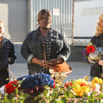 two white women and a Black woman in Good Girls stand beside one another and stare at a memorial for a fallen officer