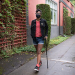 A Black non-binary person with a filtering face mask walks down a neighborhood street with one hand in their pocket and the other hand on their cane. They have a short mohawk and are wearing a jacket, shorts, tennis shoes, and glasses.