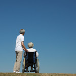 An elderly couple stands at the top of a hill. One of the people is in a wheelchair.