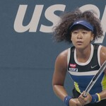 Naomi Osaka, a Black and Japanese tennis player with curly black hair pulled into a ponytail, looks at her opponent during a tennis match