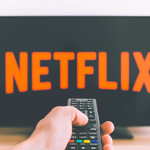 A hand points a remote at a flatscreen TV displaying the Netflix logo