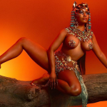 Nicki Minaj wearing a crown and crouching on a tree limb on the cover of Queen