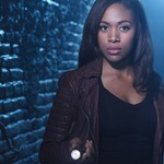 a Black woman stands in a tunnel with a flashlight