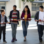 four teenagers—two Latinx and two Black—carry lunch trays and walk together