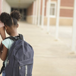 A black girl with a blue backpack holding someone's hand