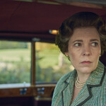 Olivia Colman, an aging white woman with short brown hair in pin curls and looks outside the car window, plays Queen Elizabeth II in The Crown