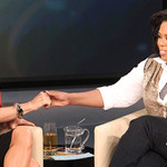 "Oprah and Jenny McCarthy sitting in armchairs next to each other, grasping hands, and smiling on ""The Oprah Winfrey Show"""