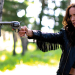 white woman wearing a leather jacket with fringe has a concerned look on her face while standing outside and pointing a gun