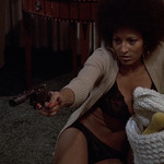 Pam Grier plays Coffy, a Black woman with an afro who's sitting on the floor and pointing a gun at an intruder, in the movie Coffy
