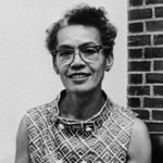a black and white photo of a Black person with short, curly hair wearing glasses and smiling at the camera