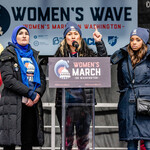 The Women's March co-chairs speak on stage during the Women's March, surrounded by signs and wearing winter clothing.