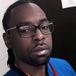 Philando Castile, a darkskinned Black man in a blue t-shirt, poses for a selfie in a bathroom