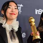 Awkwafina, an Asian woman with jet black hair, holds a Golden Globe statuette while she smiles