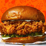 A fried chicken sandwich with pickles and mayo against an orange background