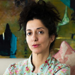Porochista Khakpour, an Iranian American writer, poses in a patterned shirt in front of a patterned background