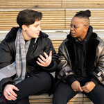 Two transmasculine people sitting together wearing coats on a bench outside and having a serious conversation.