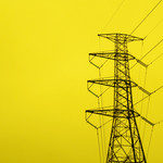 A large steel tower supporting powerlines, against a bright yellow background