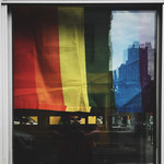 A Pride flag hanging in a window