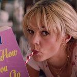 "Carey Mulligan, a white woman with blond braided pigtails, drinks a milkshake. She reads a book, titled, ""Careful How You Go."""