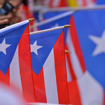 Hands holding mini Puerto Rican flags