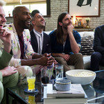 Queer Eye's Bobby Berk, Karamo Brown, Tan France, Jonathan Van Ness, and Antoni Porowski sit on a couch together and look up at a screen.