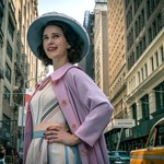 Midge Maisel, a young, white woman with brown hair, poses on a street corner