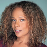 Rachel True, a Black woman with curly brown hair, poses against a turquoise background