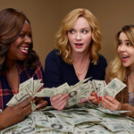 three women, one Black and two white, smile at each other while holding up bundles of money