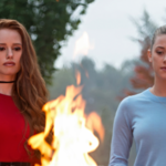 Two girls, one with red hair and red lipstick, another one white with a high blond ponytail, stand by a fire in a trash can. They both look serious.