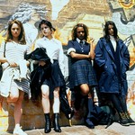 four teenagers, three white and one Black, pose side by side against a graffitied wall in The Craft