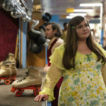 Aidy Bryant plays Annie, a white woman wears a '70s yellow dress and with a translucent cardigan while at a skating rink