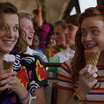 Millie Bobby Brown and Sadie Sink smile at each other while holding ice cream cones on a school bus