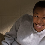 a Black woman with short hair incarcerated in a gray sweatsuit smiles