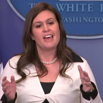 Sarah Huckabee Sanders speaking and gesturing with hands, an American flag in the background