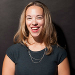 Sarah Kendzior, a white woman with shoulder-length blond hair, smiles at the camera