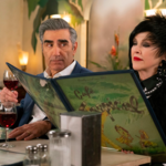 "Moira and Johnny Rose reading a menu at Cafe Tropical in ""Schitt's Creek"""